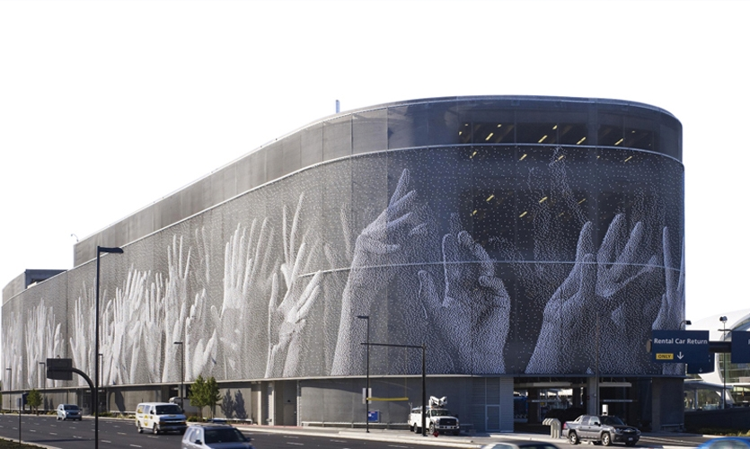 Hands, an iconic mural on the façade of San Jose International Airport's new parking garage, was created by artist Christian Moeller in collaboration with Fentress Architects. The image appears on 350,000 plastic pixels snapped to architectural metal mesh. (Photo: Nick Merrick © Hedrich Blessing/Fentress Architects)